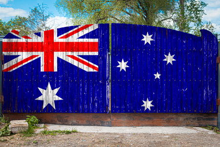 Close-up of the national flag of Australia on a wooden gate at the entrance to the closed territory on a summer day. The concept of storage of goods, entry to a closed area, tourism in Australia Stock Photo