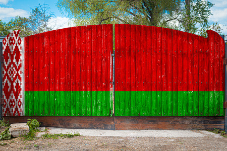 Close-up of the national flag of Belorussia on a wooden gate at the entrance to the closed territory on a summer day. The concept of storage of goods, entry to a closed area, tourism in Belarus
