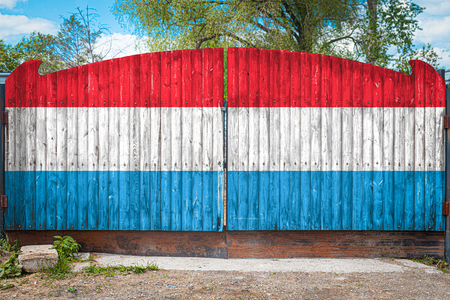 Close-up of the national flag of Luxembourg on a wooden gate at the entrance to the closed territory on a summer day. The concept of storage of goods, entry to a closed area, tourism in Luxembourg