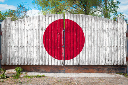 Close-up of the national flag of Japan on a wooden gate at the entrance to the closed territory on a summer day. The concept of storage of goods, entry to a closed area, tourism in Japan Stock Photo