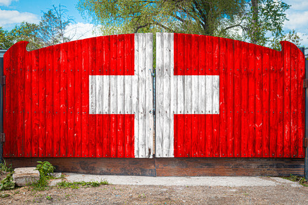 Close-up of the national flag of Switzerland on a wooden gate at the entrance to the closed territory on a summer day. The concept of storage of goods, entry to a closed area, tourism in Switzerland
