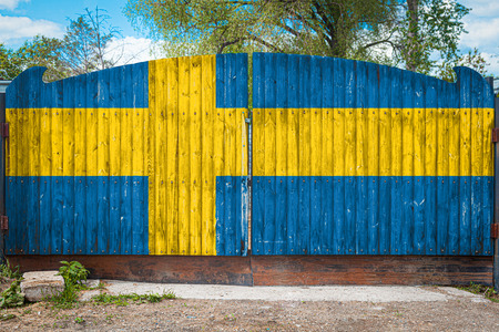 Close-up of the national flag of Sweden on a wooden gate at the entrance to the closed territory on a summer day. The concept of storage of goods, entry to a closed area, tourism in Sweden