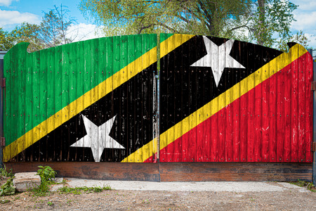 Close-up of the national flag of Saint Kitts and Nevis on a wooden gate at the entrance to the closed territory on a summer day. The concept of storage of goods, entry to a closed area, tourism in Saint Kitts and Nevis