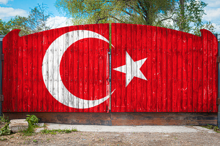 Close-up of the national flag of Turkey on a wooden gate at the entrance to the closed territory on a summer day. The concept of storage of goods, entry to a closed area, tourism in Turkey