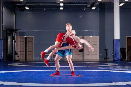 Zwei junge Männer in blau-roten Wrestling-Strumpfhosen ringen und machen ein Suplex-Wrestling auf einem gelben Wrestling-Teppich in der Turnhalle. Das Konzept des fairen Ringens