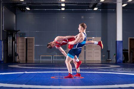 Das Konzept des fairen Ringens. Zwei griechisch-römische Wrestler in roter und blauer Uniform, die auf einem Wrestling-Teppich in der Turnhalle ringen. Das Konzept des fairen Wrestlings Standard-Bild
