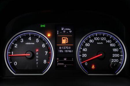 검은색 살롱이 있는 자동차의 내부 전망. 현대적인 고급 자동차 인테리어: 흰색 백라이트 및 기타 버튼이 있는 속도계, 대시보드 및 회전 속도계.소프트 포커스
