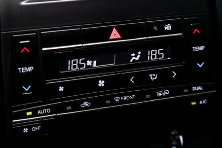 Ð¡lose-up of the car  black interior:  dashboard with temperature, clock, adjustment of the blower, air conditioner and other buttons. Banco de Imagens