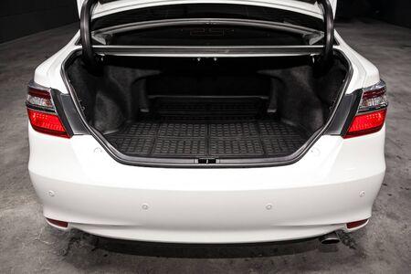 Cerrar Vista trasera de un coche sedán blanco con maletero abierto en el garaje. Baúl de coche vacío Foto de archivo