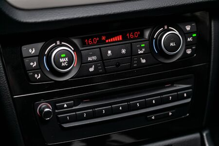 �¡lose-up of the car  black interior:  dashboard with temperature, clock, adjustment of the blower, air conditioner and other buttons.