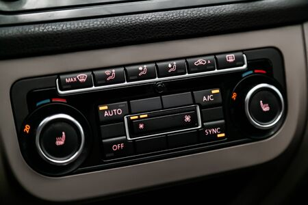 Ð¡lose-up of the car  black interior:   seat heatting buttons, adjustment of the blower, air conditioner and other buttons.