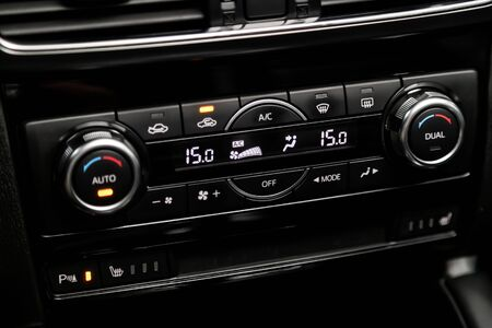�¡lose-up of the car  black interior:  dashboard with temperature, clock, adjustment of the blower, air conditioner and other buttons. Soft focus