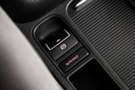 Ð¡lose-up of the car  black interior:   parking systems and auto hold buttons, soft focus