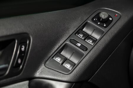 Ð¡lose-up of the car  black interior. Side door buttons: window adjustment, door lock and  side mirror adjustment buttons.  modern car interior
