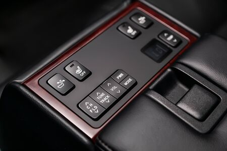 Сlose-up of the car  black interior:   seat heatting and adjustment, volume, true track  buttons,  temperature regulator and other buttons. Soft focus