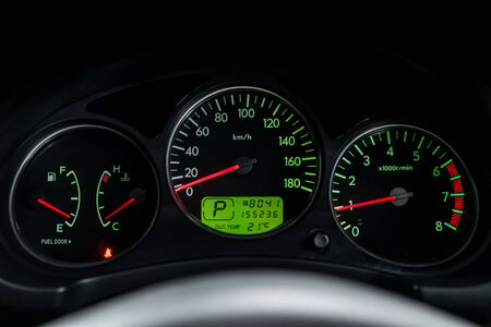 Interior view of car with black salon. Modern luxury prestige car interior: speedometer, dashboard and tachometer  with green backlight and other buttons. Soft focus Stock Photo
