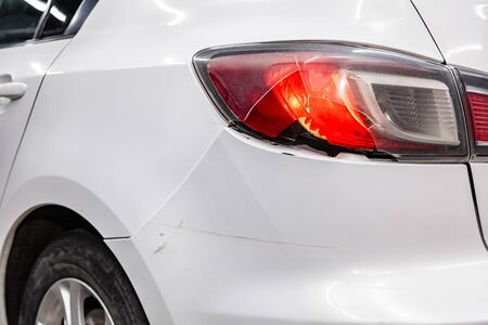 White sedan with a sporty and modern design shines headlamp, close-up. Concept of expensive car. Close-up of headlights, bumper and car wheels
