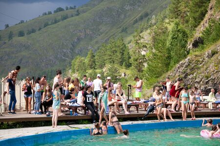 Altai, Russia – August 08, 2018:  The company of children and teenagers in summer clothes and swimsuits rests and bathes in the pool at the summer international camp in the Chemal region, Altai Territory Standard-Bild - 133072793