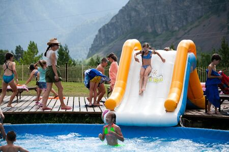 Altai, Russia – August 08, 2018:  The company of children and teenagers in summer clothes and swimsuits rolls off an inflatable slide and basks in the pool at the summer international camp in the Chemalsky District, Altai Territory Standard-Bild - 133072797