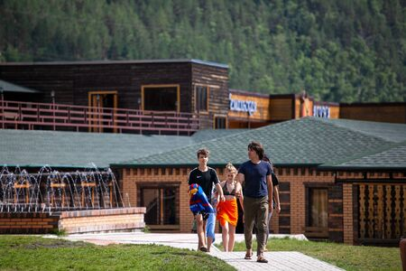 Altai, Russia – August 08, 2018:  a company of teenagers walks and goes to the pool in bathing suits at the summer international camp in the Chemalsky District, Altai Territory Standard-Bild - 133072799