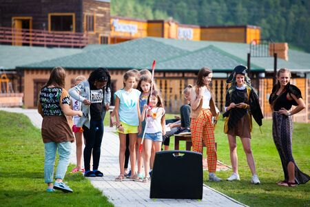 Altai, Russia – August 08, 2018:  a company of teenagers of children of different nationalities archery, having fun and playing at the summer international camp in the Chemalsky region, Altai Territory, view through fountain drops Standard-Bild - 133072801
