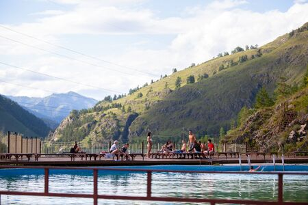 Altai, Russia – August 08, 2018:  The company of children and teenagers in summer clothes and swimsuits rests and bathes in the pool at the summer international camp in the Chemal region, Altai Territory Standard-Bild - 133072803