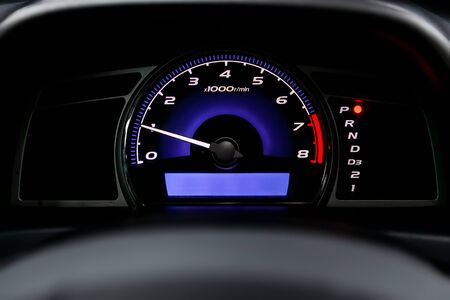Interior view of car with black salon. Modern luxury prestige car interior: speedometer, dashboard and tachometer  with white backlight and other buttons. Soft focus