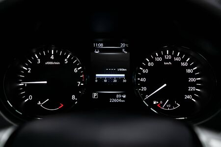Car dashboard wuth white backlight: Odometer, speedometer, tachometer, fuel level, water temperature and more