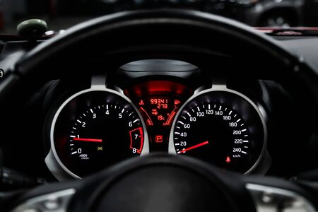 Car dashboard wuth red backlight: Odometer, speedometer, tachometer, fuel level, water temperature and more. Modern car interior: parts, buttons, knobs Stock Photo