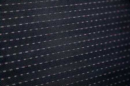 Close-up black car seat trim. Soft rough carbon fabric texture.