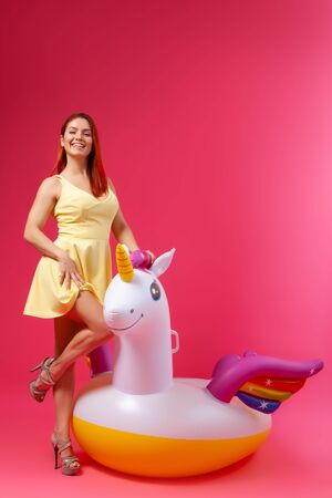 Summer Fashion beautiful woman in summer clothes having fun, smilling and posing with balloons On Unicorn Float on isolated pink background Reklamní fotografie