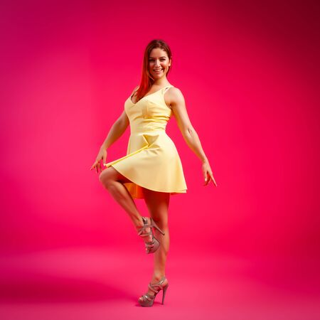 Beautiful woman with healthy body wearing in a dress dancing and spinning around on pink background.The concept of summer fashion clothes and relaxation. pink and joyful mood.