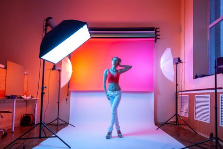 Backstage: model woman with in underwear,  jeans posing in attractive position in colorful bright neon yellow and pink lights in studio. Fashion concept