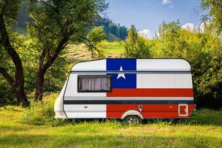 A car trailer, a motor home, painted in the national flag of Chile stands parked in a mountainous. The concept of road transport, trade, export and import between countries. Travel by car