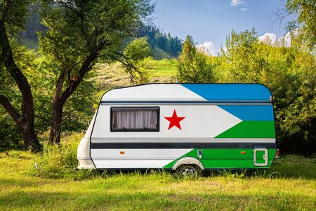A car trailer, a motor home, painted in the national flag of Djibouti stands parked in a mountainous. The concept of road transport, trade, export and import between countries. Travel by car