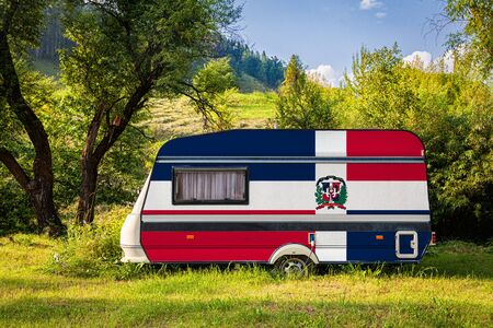 A car trailer, a motor home, painted in the national flag of Dominicana stands parked in a mountainous. The concept of road transport, trade, export and import between countries. Travel by car