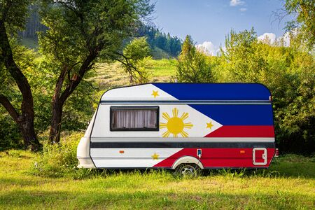 A car trailer, a motor home, painted in the national flag of Philippines stands parked in a mountainous. The concept of road transport, trade, export and import between countries. Travel by car