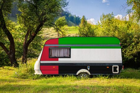 A car trailer, a motor home, painted in the national flag of United Arab Emirates stands parked in a mountainous. The concept of road transport, trade, export and import between countries. Travel by car