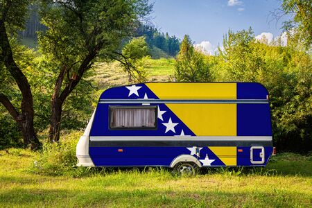 A car trailer, a motor home, painted in the national flag of Bosnia Herzegovina stands parked in a mountainous. The concept of road transport, trade, export and import between countries. Travel by car Фото со стока
