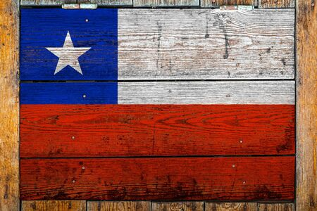 National flag of Chile on a wooden wall background.The concept of national pride and symbol of the country.Flag painted on a wooden fence with metal nails.