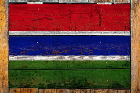 National flag of Gambia on a wooden wall background.The concept of national pride and symbol of the country.Flag painted on a wooden fence with metal nails.