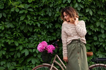 Beautiful dark-haired woman in sweater and beige skirt smiling, posing and  standing next to a bicycle with a large bouquet of peonies against a background of a vine-covered wall