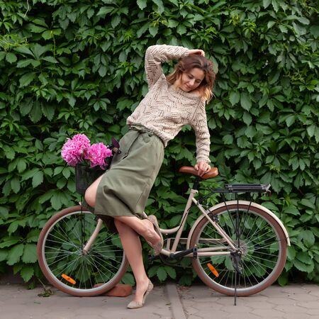 A young dark-haired woman in sweater and a beige skirt  sitting on beige retro bicycle  with bouquet of pink peonies in a wicker basket on the background of a vine-covered wall