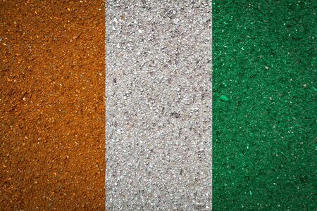 National flag of Cote dIvoire on a stone background.The concept of national pride and symbol of the country.