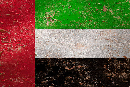 National flag of United Arab Emirates  on old peeling wall background.The concept of national pride and symbol of the country.