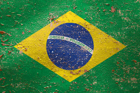 National flag of Brazil on old peeling wall background.The concept of national pride and symbol of the country.