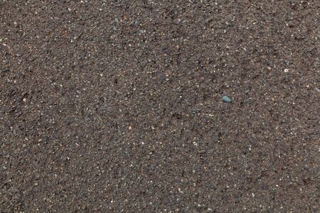 Close-up of sand from the river, mixed with small stones. The texture of gray dark sand, the background. Imagens