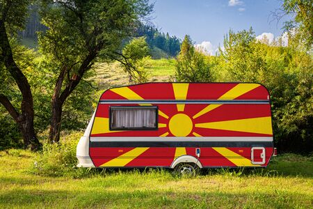 A car trailer, a motor home, painted in the national flag of Macedonia stands parked in a mountainous. The concept of road transport, trade, export and import between countries. Travel by car