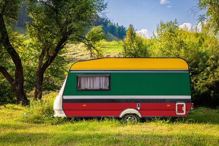 A car trailer, a motor home, painted in the national flag of Lithuania stands parked in a mountainous. The concept of road transport, trade, export and import between countries. Travel by car 版權商用圖片