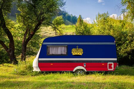 A car trailer, a motor home, painted in the national flag of Liechtenstein stands parked in a mountainous. The concept of road transport, trade, export and import between countries. Travel by car 版權商用圖片